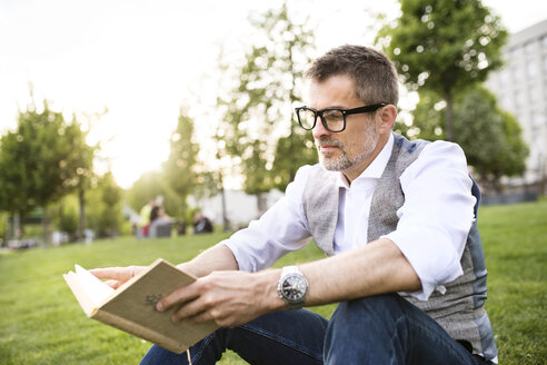 Confident mature businessman in the city park sitting on grass reading book - HAPF01739