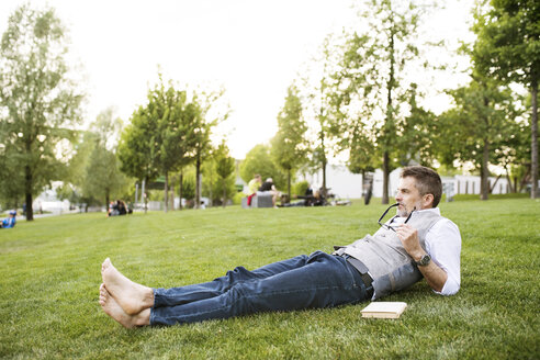 Mature businessman in the city park lying on grass - HAPF01742