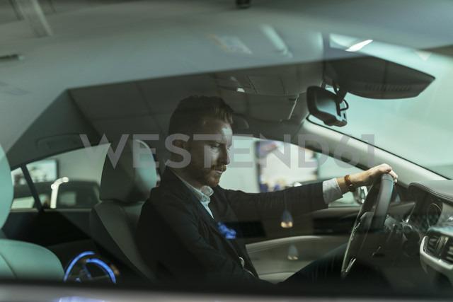 Businessman testing car in car dealership - ZEDF00658