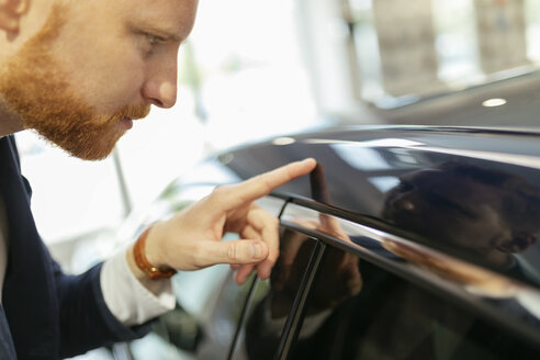 Customer touching car paint with his finger - ZEDF00664