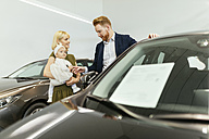 Family in car dealership choosing family vehicle - ZEDF00667