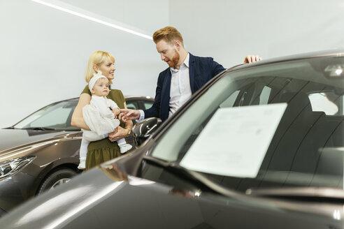 Family in car dealership choosing family vehicle - ZEDF00667