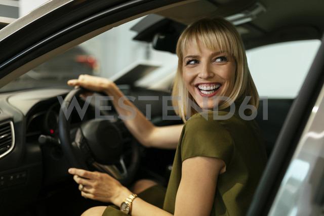 Blond woman choosing new car in car dealership - ZEDF00673