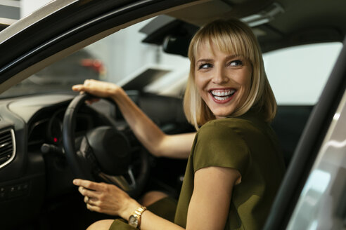 Blond woman choosing new car in car dealership - ZEDF00673