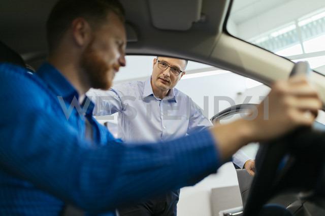 Customer in car dealership testing car - ZEDF00682