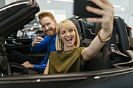 Couple taking selfies, sitting in convertible in car dealership - ZEDF00691
