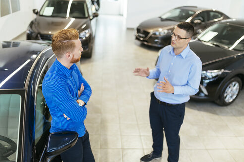 Salesman advising customer in car dealership - ZEDF00700
