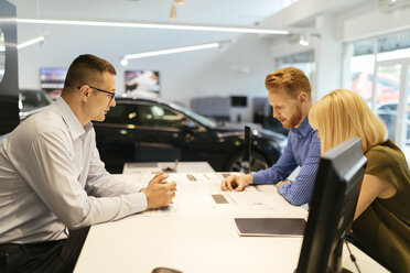 Salesperson advising couple in car dealership - ZEDF00706