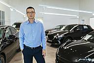 Car dealer standing in his shop - ZEDF00712