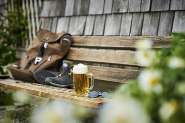 Germany, Bavaria, glass of beer, backpack, sunglasses and hiking shoes on wooden bench - DIKF00249
