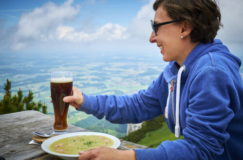 Germany, Chiemgau, happy hiker on Hochfelln with glass of beer and dish of pea soup - DIKF00252
