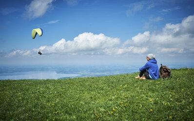 Germany, Chiemgau, hiker sitting on Alpine meadow watching paraglider - DIKF00255
