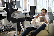 Businessman in bean bag in office eating pizza and using tablet - PESF00691