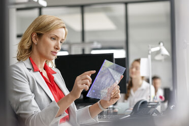Businesswoman at desk in office using futuristic tablet - PESF00715