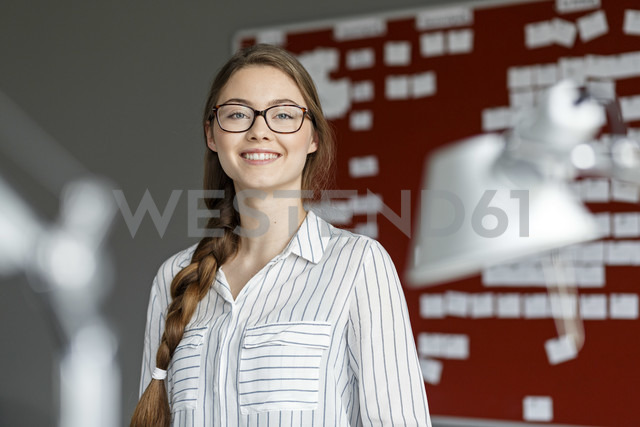 Portait of smiling young woman in office in front of scrum board - PESF00721 - Peter Scholl/Westend61
