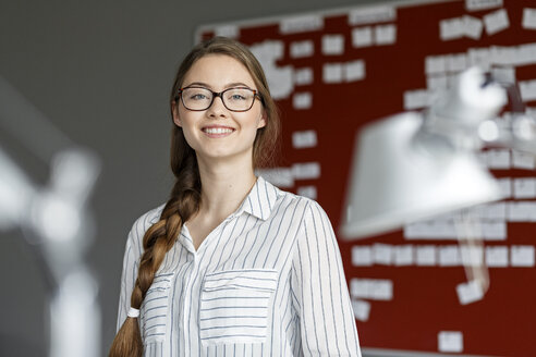 Portait of smiling young woman in office in front of scrum board - PESF00721