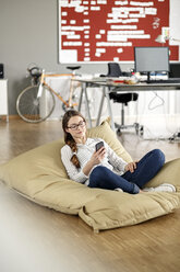 Young woman with cell phone sitting in bean bag in office - PESF00724