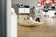 Young woman with cell phone lying in bean bag in office - PESF00727