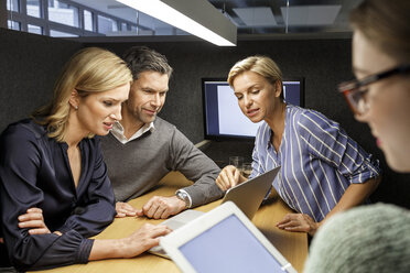 Colleagues with laptop and tablet having a meeting in meeting box - PESF00742