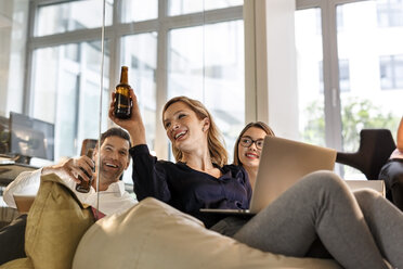 Casual business people clinking beer bottles in office - PESF00745