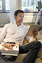 Businessman in bean bag in office eating pizza and using tablet - PESF00748