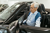 Senior man testing convertible in car dealership - ZEDF00716