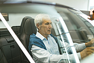 Senior man testing convertible in car dealership - ZEDF00719