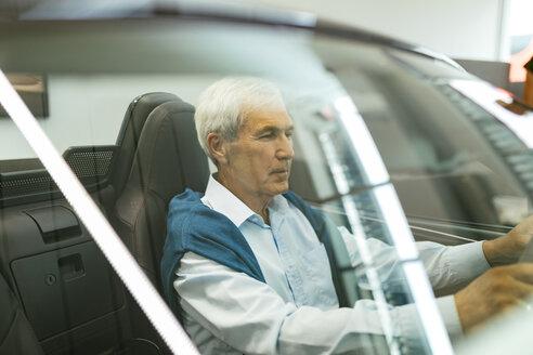 Senior man testing convertible in car dealership - ZEDF00719