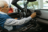 Senior man testing convertible in car dealership - ZEDF00722