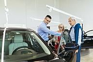 Senior couple couple talking with salesperson in car dealership - ZEDF00725