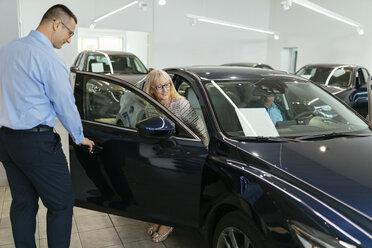 Salesman advising customers in car dealership - ZEDF00728