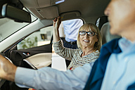 Senior couple trying out car in car dealership - ZEDF00731
