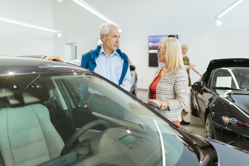Couple looking at car in dealeship - ZEDF00734