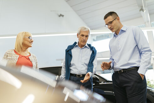 Senior couple couple talking with salesperson in car dealership - ZEDF00740
