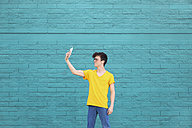 Young man taking a selfie with smartphone in front of blue brick wall - RTBF00908