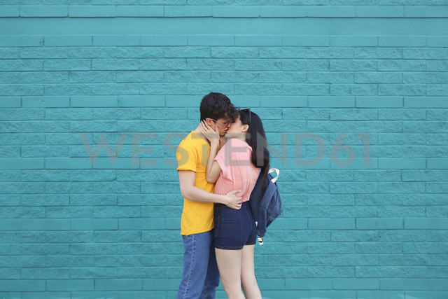 Young couple kissing in front of blue brick wall - RTBF00911