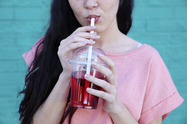 Young woman drinking soft drink, partial view - RTBF00920