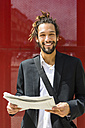 Portrait of young businessman with dreadlocks reading newspaper - MGIF00014