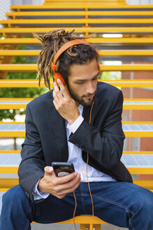 Young businessman with dreadlocks sitting on stairs listening music with headphones and cell phone - MGIF00017