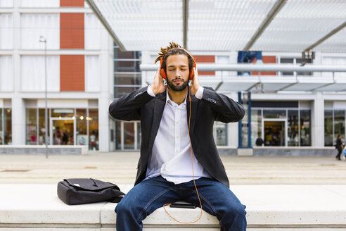Portrait of young businessman with dreadlocks listening music with headphones and cell phone - MGIF00023