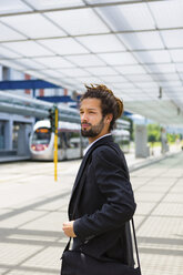 Portrait of young businessman with dreadlocks waiting at station - MGIF00026