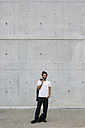 Smiling young businessman with dreadlocks standing in front of concrete wall - MGIF00029