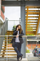 Portrait of young businessman with dreadlocks on the phone - MGIF00035