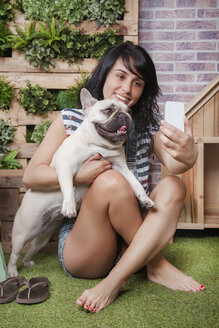 Woman and french bulldog taking a selfie on the terrace - RTBF00925