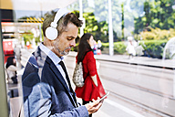 Businessman with smartphone and headphones waiting at the bus stop - HAPF01745