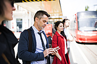 Businessman with smartphone waiting at the bus stop - HAPF01751