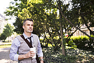 Mature businessman with coffee in city park - HAPF01754
