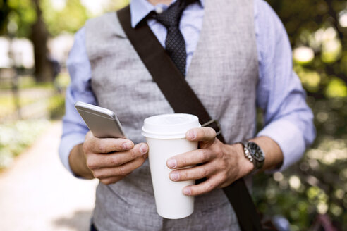 Close-up of businessman with coffee and smartphone in city park - HAPF01757