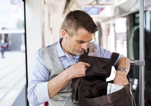 Businessman with earphones and bag travelling in tram - HAPF01763