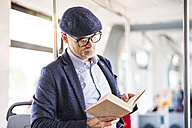 Man in bus reading book - HAPF01772